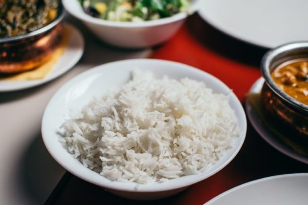 Bowl of rice with toppings in the background